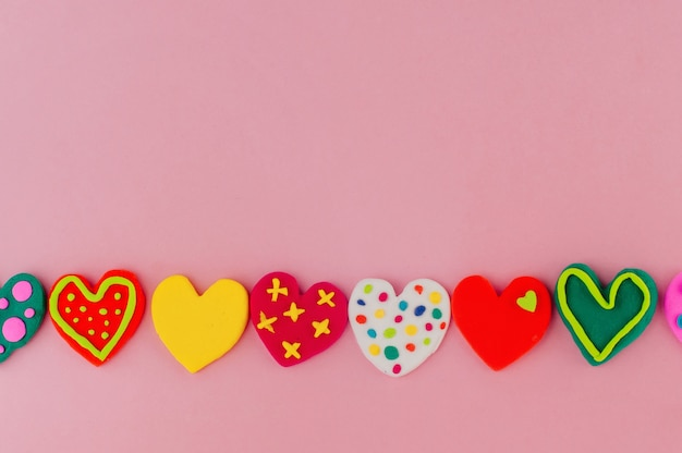 Series of colorful handmade plasticine hearts on pink