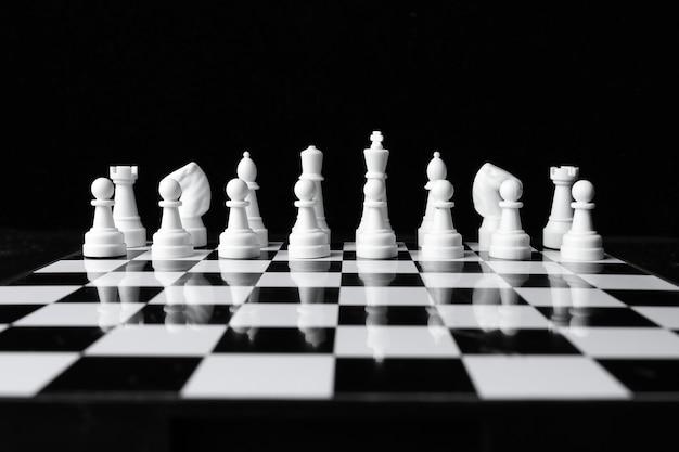 Серия белых шахматных фигур перед игрой на черно-белой доске на черном фоне.