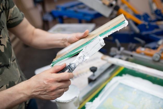 洋服工場でのセリグラフィーシルクスクリーン印刷工程 クレンジングフレーム スキージとプラスチゾルカラー塗料