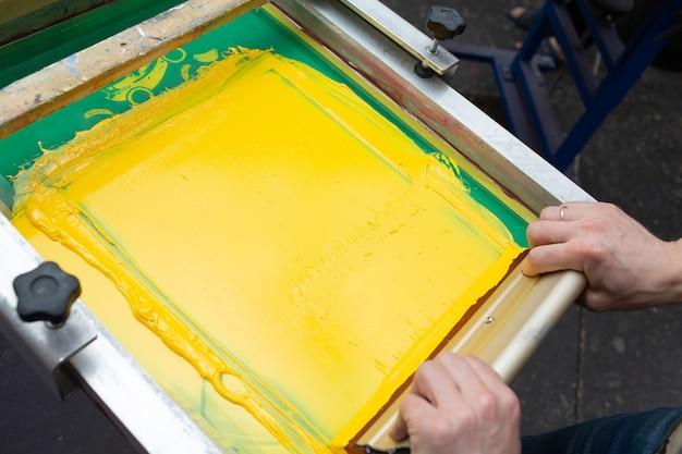 衣料品工場でのセリグラフィーシルクスクリーン印刷プロセス。フレーム、スキージ、プラスチゾルのカラーペイント
