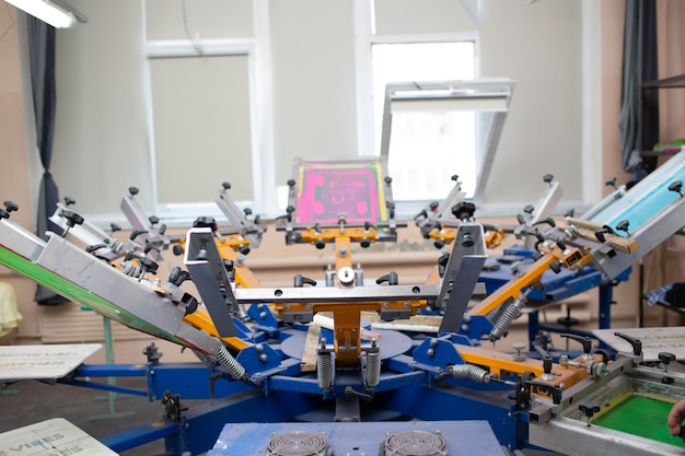 Serigraphy silk screen print process at clothes factory carousel frame squeegee and plastisol color paints