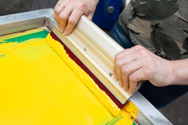 Serigraphy silk screen print process at clothes factory frame squeegee and plastisol color paints
