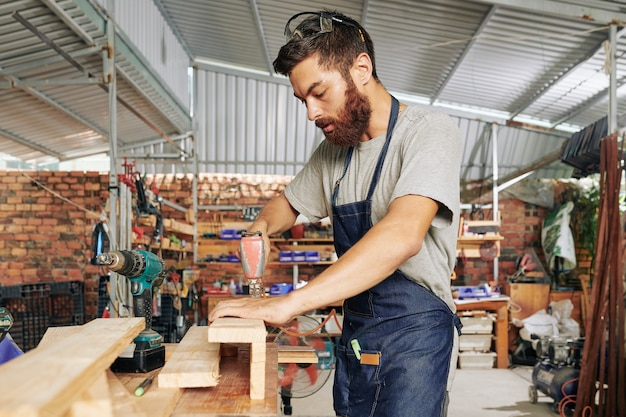 Serioius bearded carpender using drill when joining wooden blocks and making furniture