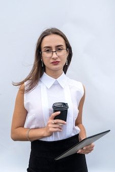 Serios businesswoman with cup of coffee and tablet computer isolated on white grey  background