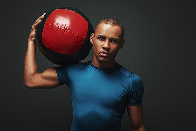 Serious about staying in a good shape close up of sportsman standing with a ball