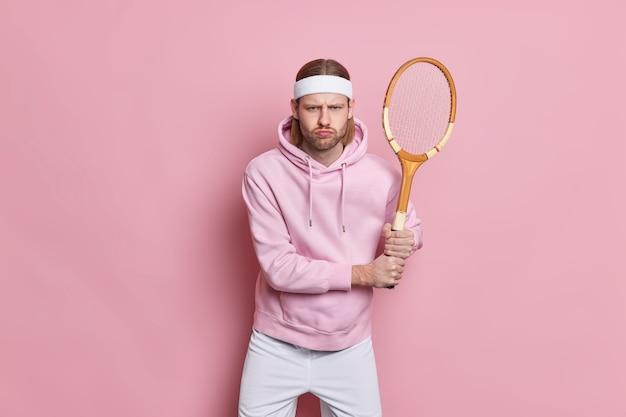 테니스 라켓을 든 진지한 활동적인 스포츠맨 스탠드가 좋아하는 게임이 건강을 위해 스포츠에 들어갑니다.