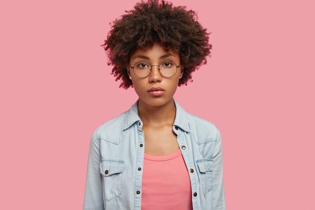La femmina afroamericana adorabile seria con capelli ricci, vestita in giacca di jeans alla moda, posa contro il muro rosa, ascolta le informazioni necessarie. concetto di persone, bellezza ed etnia