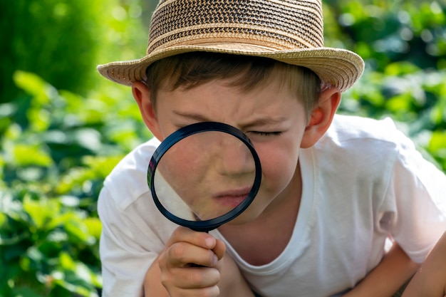 Serious adorable little child boy in straw hat with magnifying glass watching or looking for. kid conducts investigation, undergoes quest. little detective.