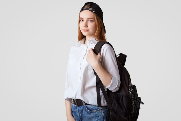 Serious adorable teenager in stylish black hat, carries rucksack, wears white shirt and jeans, isolated on white. schoolgirl prepares for school. education concept