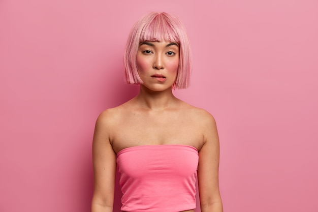 Serious adorable woman with eastern appearance, pink bob hairstyle, wears tank top, bites lips and looks directly, thinks about good decision, has mysterious expression. fashion girl