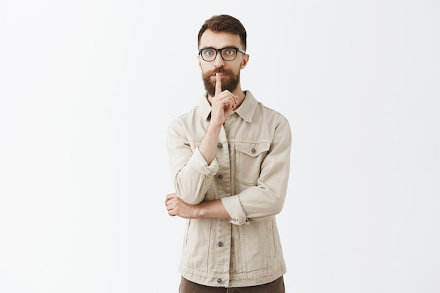 Серьезный взрослый бородатый мужчина в очках позирует у белой стены