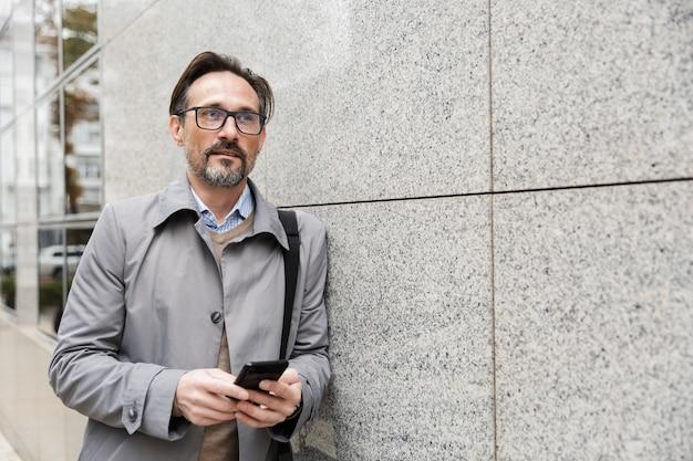 Серьезный взрослый бизнесмен в очках с помощью мобильного телефона, опираясь на стену на открытом воздухе