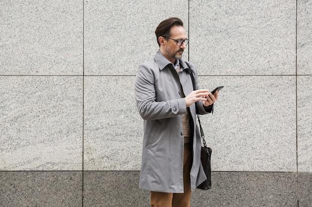Серьезный взрослый бизнесмен в очках с помощью мобильного телефона, стоя возле здания на городской улице