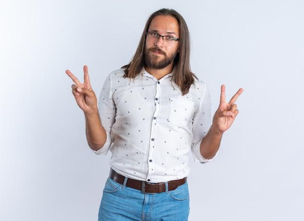 Серьезный взрослый красивый мужчина в очках делает знак мира