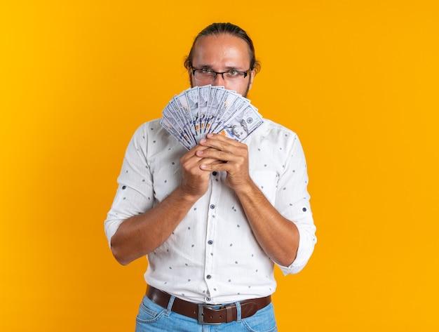 Un bell'uomo adulto serio con gli occhiali che tiene i soldi guardando la telecamera da dietro isolato sul muro arancione