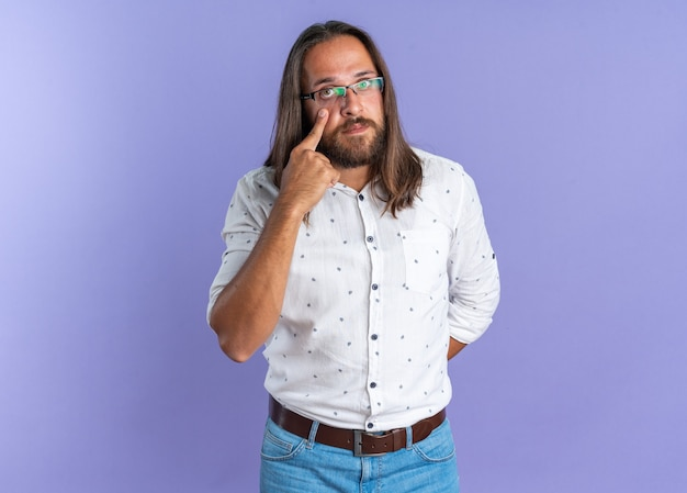 Serious adult handsome man wearing glasses keeping hand behind back looking at camera pulling down lower eye lid isolated on purple wall with copy space