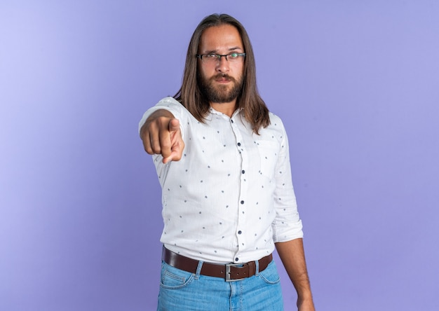 Serious adult handsome man wearing glasses looking and pointing at camera isolated on purple wall with copy space