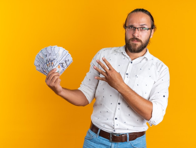 Serious adult handsome man wearing glasses showing money looking at camera showing four with hand isolated on orange wall