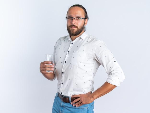 水のガラスを保持している腰に手を保ち、縦断ビューで立っている眼鏡をかけている深刻な大人のハンサムな男