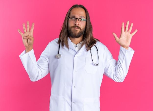 Medico maschio adulto serio che indossa accappatoio medico e stetoscopio con gli occhiali che guarda l'obbiettivo che mostra nove con le mani isolate sulla parete rosa
