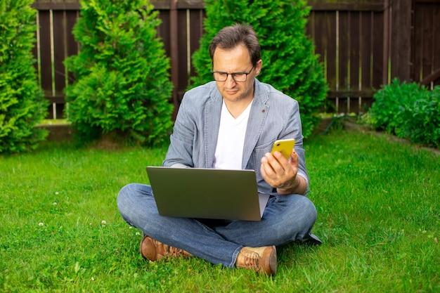 屋外の芝生に座っている真面目な成人男性、コンピューターのラップトップで作業し、携帯電話で入力している魅力的な男性のフリーランサー、夏の朝に自宅で仕事をしているビジネスマン。在宅勤務、ライフスタイル