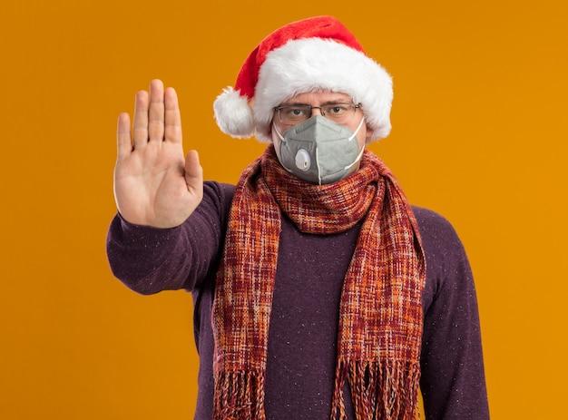Serio uomo adulto che indossa occhiali maschera protettiva e cappello santa con sciarpa intorno al collo guardando la telecamera facendo gesto di arresto isolato su sfondo arancione