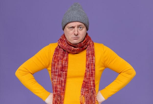 冬の帽子と首にスカーフを腰に手を置いて見ている深刻な大人の男