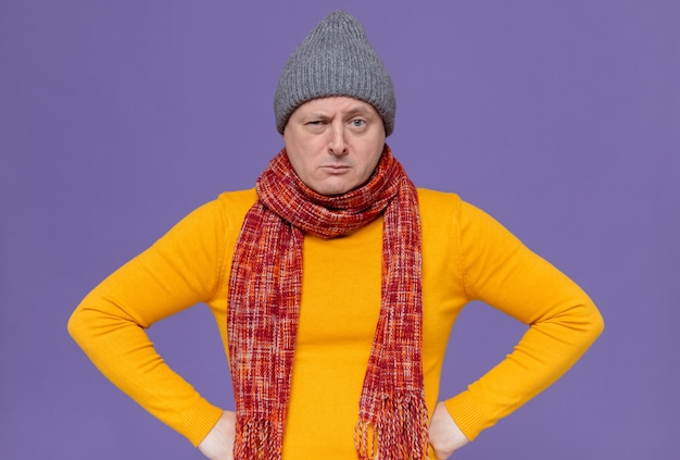 Serious adult man with winter hat and scarf around his neck putting hands on his waist and looking