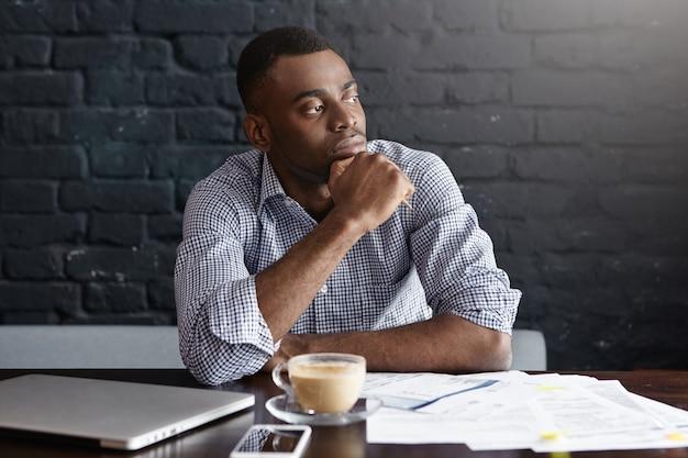 カフェでコーヒーを飲んでいる深刻なアフリカ系アメリカ人のビジネスマン