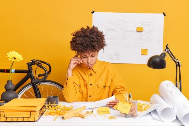 Серьезная афроамериканка, студентка инженерного факультета, внимательно смотрит на документы, думает о творческом решении, беспорядок на рабочем месте