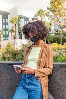 코로나바이러스 동안 아프리카 헤어스타일과 보호용 마스크를 쓰고 거리에 서서 휴대전화로 메시지를 보내는 진지한 아프리카계 미국인 여성