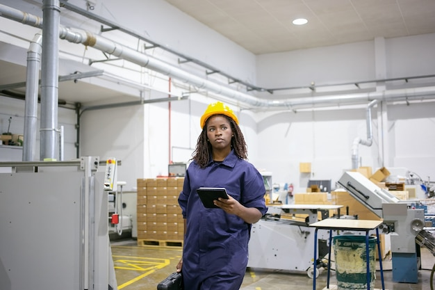 Serious african american female worker in protective uniform walking to workplace on plant floor, holding tablet and case with tools