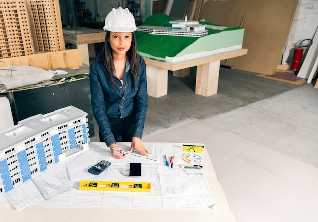 Serious african-american lady in safety helmet standing near model of building on table