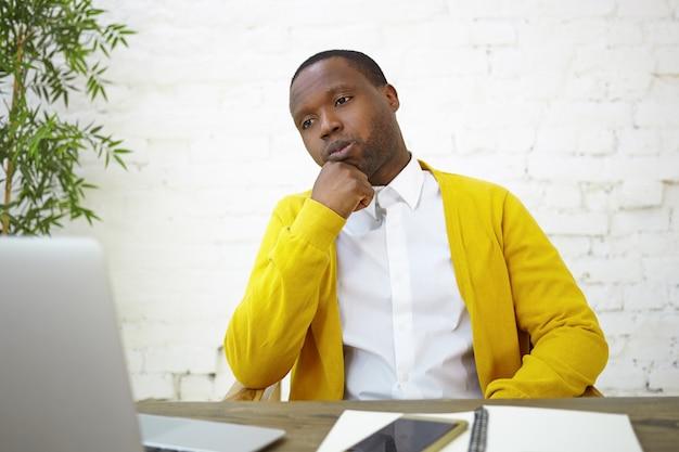 Grave impiegato maschio afroamericano vestito elegantemente seduto al muro di mattoni bianchi al suo posto di lavoro, utilizzando un computer portatile generico, strofinando il mento, avendo un'espressione facciale premurosa