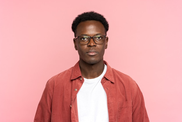 Serious african american man in glasses wear red shirt, looking at camera standing isolated on pink