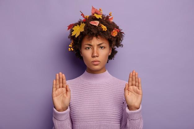La donna afroamericana seria aggrotta le sopracciglia e mostra il gesto di fermarsi, indossa un caldo maglione lavorato a maglia, tiene i palmi distesi davanti alla telecamera, ha le foglie autunnali bloccate tra i capelli ricci. stagione, linguaggio del corpo