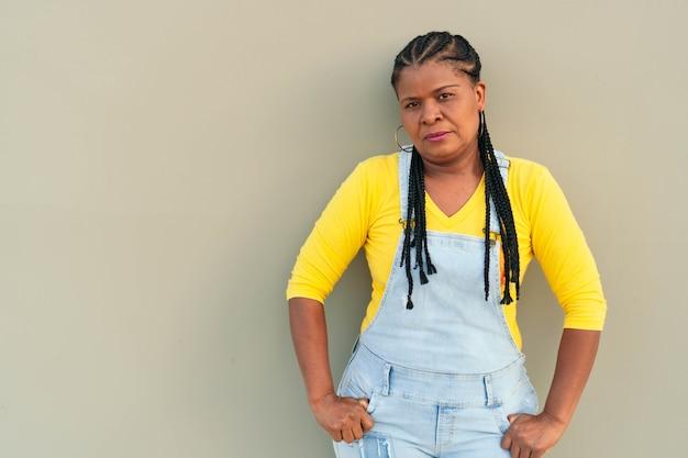 灰色の壁にもたれて深刻なアフリカ系アメリカ人の女性