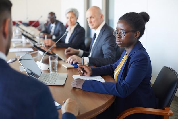 Серьезная африканская деловая женщина слушает спикера и делает заметки в документе, сидя на конференции