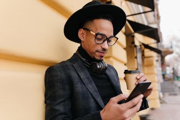 커피를 마시는 동안 인터넷에서 뉴스를 읽는 심각한 아프리카 남자. 전화와 라떼 건물 근처에 서 세련 된 모자에 집중된 흑인 젊은 남자의 야외 사진.