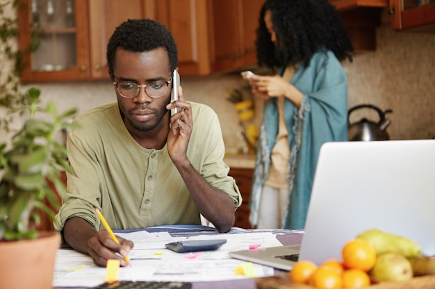 Serious african man having phone conversation with bank asking to extend loan term for paying out mortgage, holding pencil in the other hand, making notes in documents, lying on table in front of him