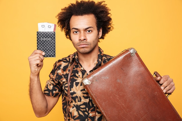 Serious african man holding passport and suitcase.