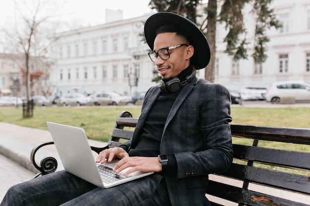 オープンスカイの下でラップトップを使用して黒いシャツとズボンの深刻なアフリカ人。公園のベンチで休んでいるムラートフリーランサーの屋外写真。