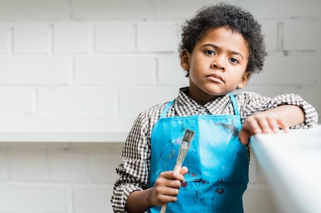 スタジオや教室でカメラの前に立っている間絵筆を手で押し青いエプロンで深刻なアフリカの少年