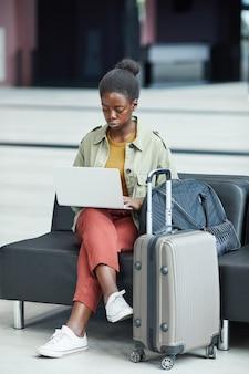 Серьезная африканская женщина, работающая на портативном компьютере, сидя в аэропорту