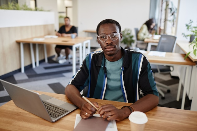 Serious africanamerican businessman in glasses sitting at table in open space office with opend lapt...