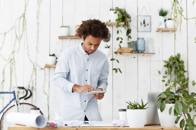 ファンキーなヘアスタイルがオフィスに対して立っている深刻なアフロアメリカンのエンジニア、デザイナー、または建築家