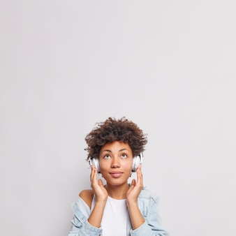 Serious afro american female student listens lecture or webinar online via headphones focused above enjoys good sound wears denim shirt poses against white wall copy space for advertisement