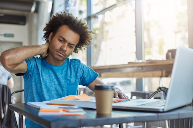 Serious afro american male student in blue t-shirt sitting at cafeteria drinking takeaway coffee working at his project using books and laptop touching his neck with hand having pain