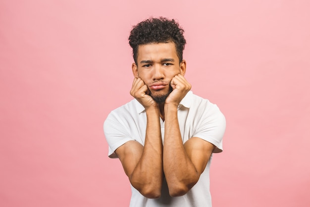 Serious afro american man thinking isolated over pink background.