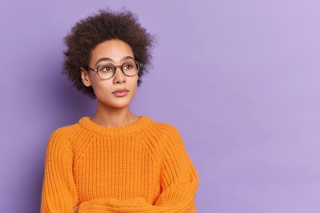 심각한 아프리카 계 미국인 십대는 광학 안경 오렌지 니트 스웨터를 착용하고 어딘가에 집중된 사려 깊은 포즈로 스탠드를 교차시킵니다.